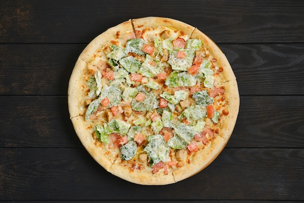 Pizza con carne di pollo fritto, lattuga e pomodoro sul tavolo di legno scuro