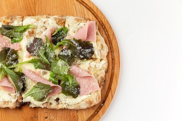 Pizza con prosciutto su una tavola di legno. un appetitoso spuntino tradizionale. sfondo bianco. spazio per il testo.