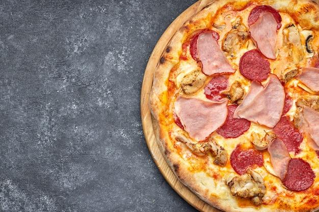 Pizza con carne, salsiccia, carne e funghi su uno sfondo grigio con posto per il testo. pizza 4 carni