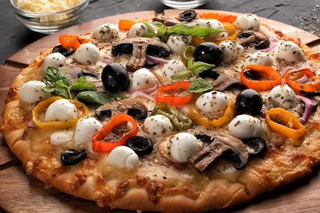 Pizza con mozzarella, olive e funghi. cucina italiana. ingredienti per fare la pizza su uno sfondo nero. concetto per la pubblicità di ristoranti o pizzerie.