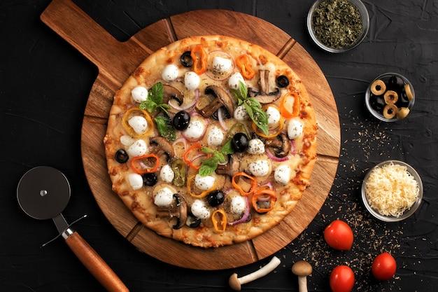 Pizza con mozzarella, olive e funghi. cucina italiana. ingredienti per fare la pizza su uno sfondo nero. vista dall'alto concetto per la pubblicità di ristoranti.
