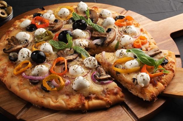 Pizza con mozzarella, olive e funghi. cucina italiana. ingredienti per fare la pizza su una tavola nera. vista dall'alto concetto per pizzerie pubblicitarie.
