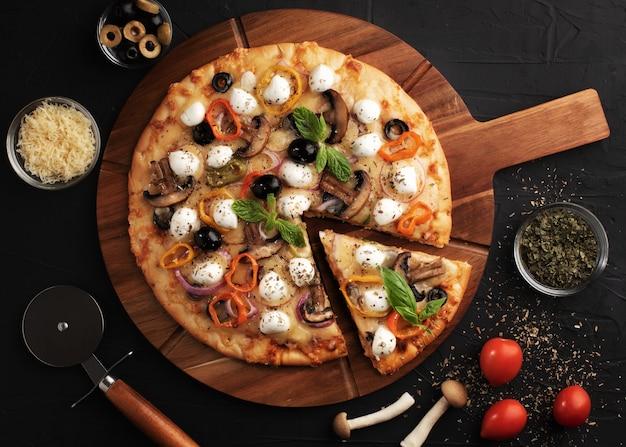 Pizza con mozzarella, olive e funghi. cucina italiana. ingredienti per fare la pizza Foto Premium