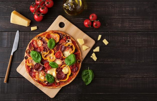 Pizza con mozzarella e salame su uno sfondo di legno scuro