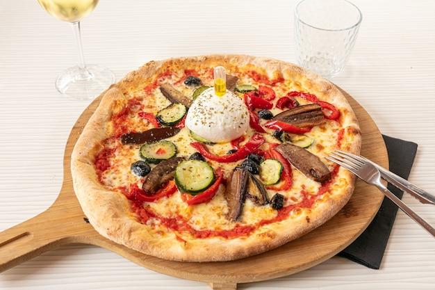 Pizza con mozzarella e verdure servita su tagliere