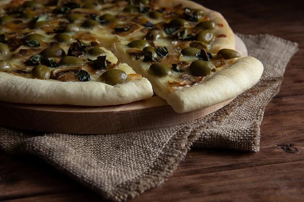 Pizza con funghi e olive su un tavolo di legno