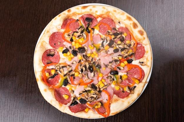 Pizza con peperoni e funghi, prosciutto e peperone dolce