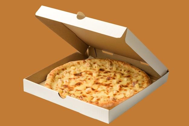 Pizza con ananas in una scatola di cartone isolato su sfondo.