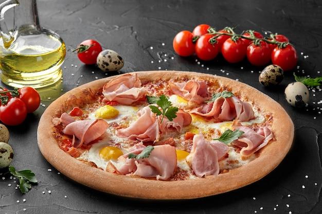 Pizza con uova di quaglia e prosciutto cotto su superficie nera