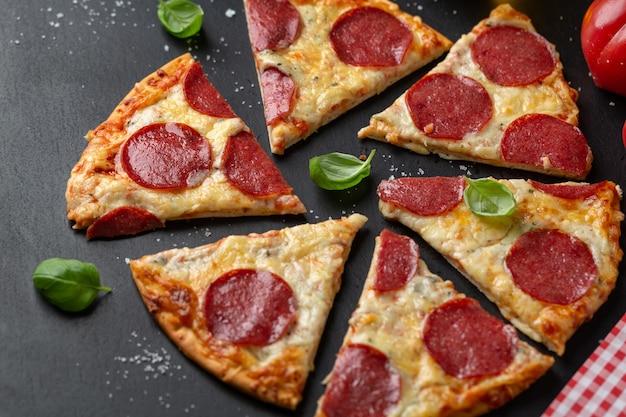 Pizza con salame e formaggio su superficie scura