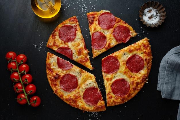 Pizza con salame e formaggio sul tavolo scuro. vista dall'alto con copia spazio.