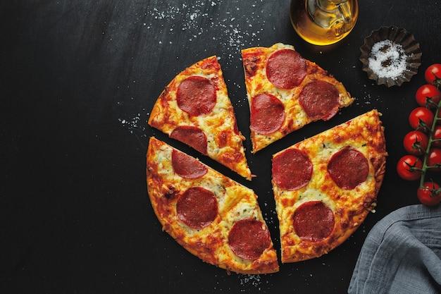 Pizza con salame e formaggio sulla scatola della pizza sul tavolo scuro.