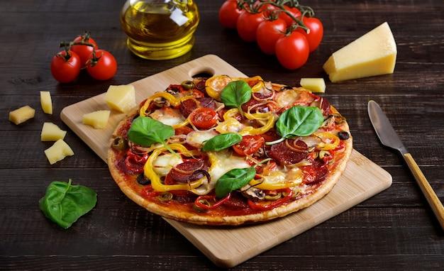 Pizza con salame e mozzarella su uno sfondo di legno scuro