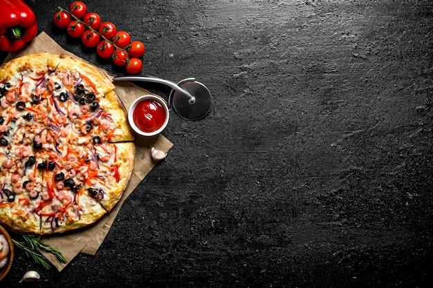 Pizza con frutti di mare e pomodorini su tavola rustica nera.