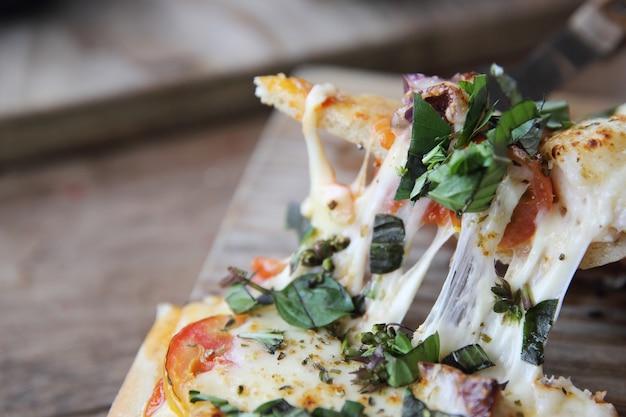 Pizza con frutti di mare e pomodori su un tavolo di legno, cibo italiano