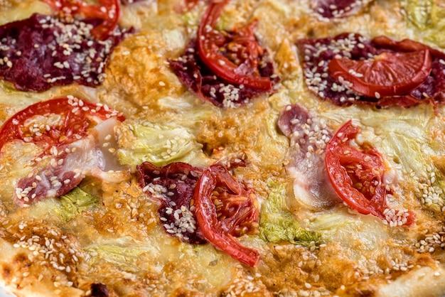 Pizza con pomodoro, prosciutto, formaggio e salsa. macro