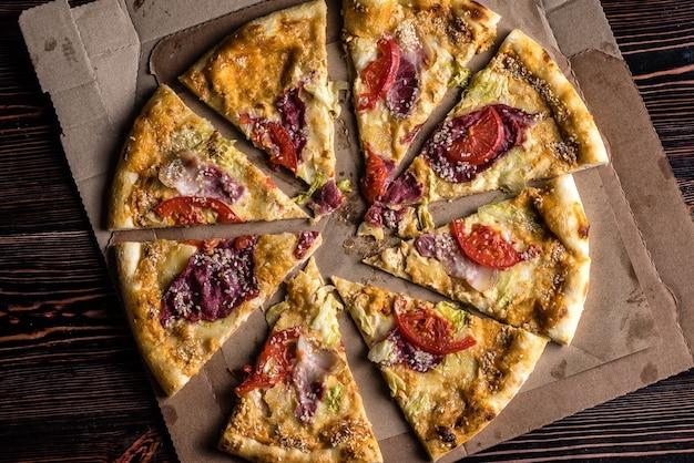 Pizza con pomodoro, prosciutto, formaggio su un tavolo di legno