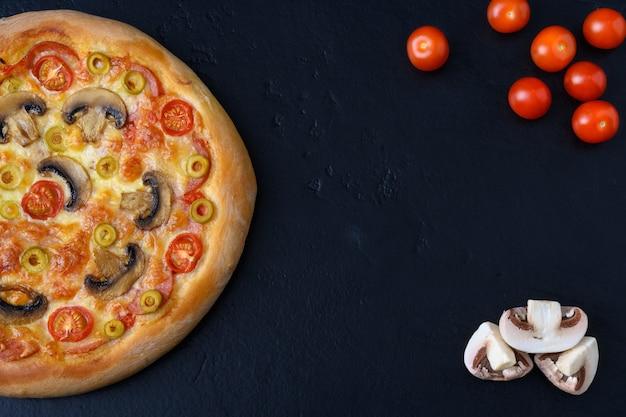 Pizza con pomodoro, mozzarella, salame, funghi e olio su fondo nero