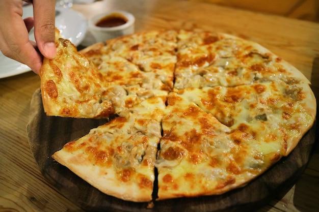 Pizza su piatto di legno con fetta di pizza raccolta a mano. concetto di cibo.