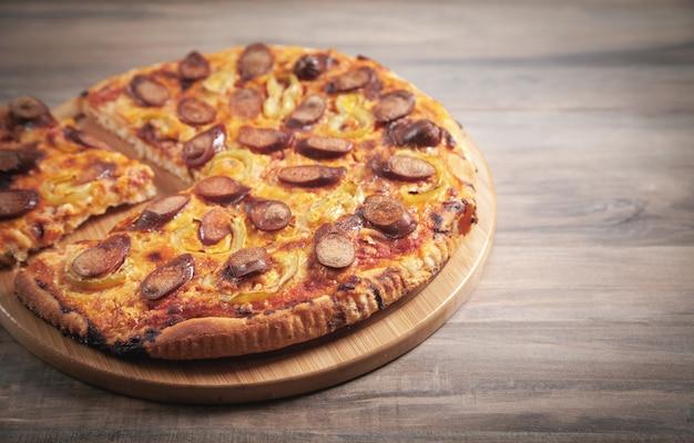Pizza sul fondo della tavola in legno.