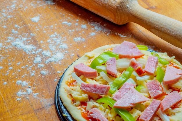 Pizza su un tavolo di legno cosparso di farina