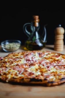 Una pizza su un tavolo di legno. ci sono origano, olio d'oliva e pepe in sottofondo.