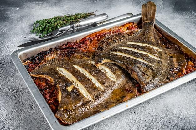 Pesce piatto di platessa o passera di mare al forno in salsa di pomodoro in teglia. vista dall'alto.