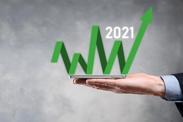 Pianificare la crescita del business nell'anno 2021 concetto. piano di uomo d'affari e aumento di indicatori positivi nella sua attività, crescendo concetti di business.