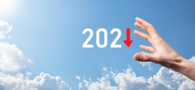 Pianificare la crescita negativa del business nel concetto dell'anno 2021. il piano dell'uomo d'affari e l'aumento degli indicatori negativi nella sua attività, declinano i concetti di business. tenere la mano sullo sfondo del cielo