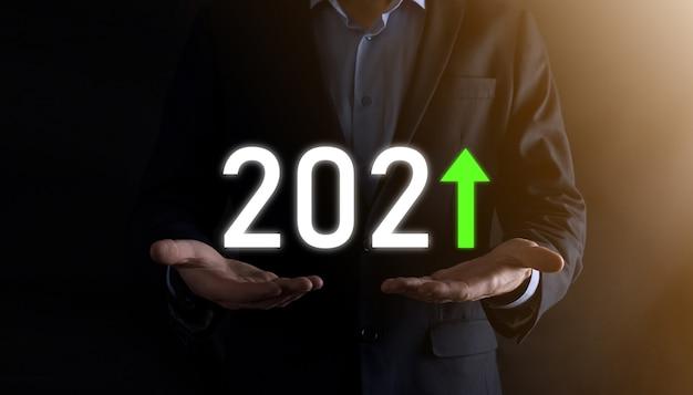 Pianificare la crescita positiva del business nell'anno 2021. piano dell'uomo d'affari e aumento degli indicatori positivi nella sua attività, crescendo concetti di business.