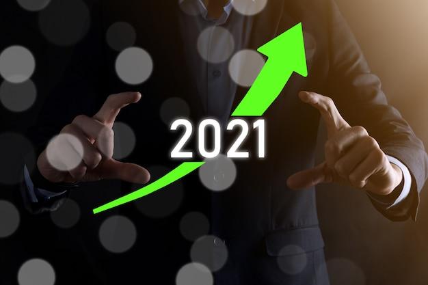 Pianificare la crescita positiva del business nel concetto di anno 2021. piano dell'uomo d'affari e aumento degli indicatori positivi nella sua attività, crescendo concetti di business.