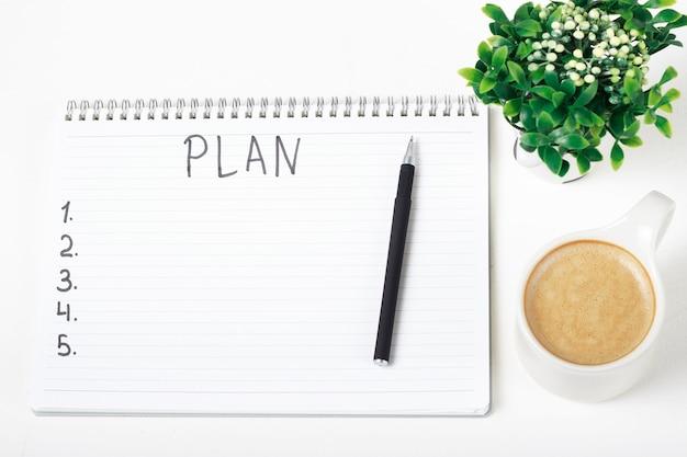 Piano su notebook, pianta e tazza di caffè