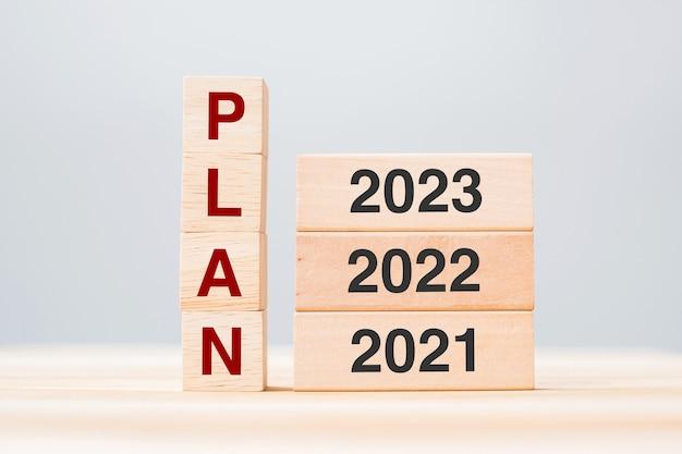 Pianifica il testo con blocchi di legno 2023, 2022 e 2021 sullo sfondo della tabella. gestione del rischio, risoluzione, strategia, soluzione, obiettivo, capodanno nuovo te e concetti di buone feste happy