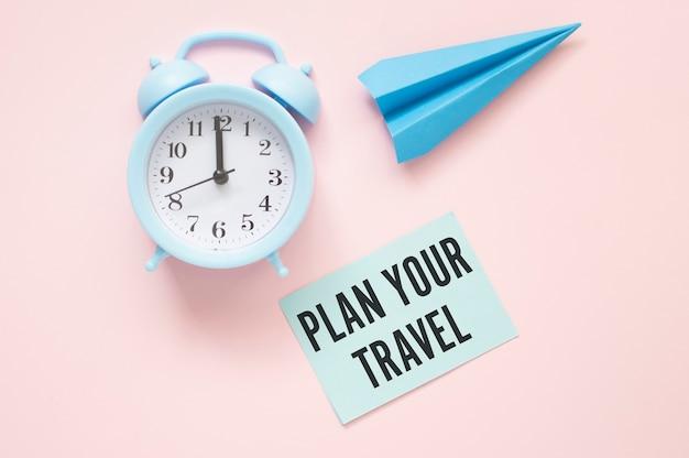 Pianifica il tuo testo di viaggio su carta con orologio e aeroplano di carta su un tavolo rosa.