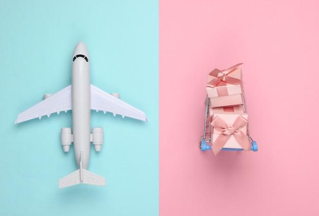 Statuetta di aereo, carrello della spesa e scatole regalo su pastello rosa blu. lay piatto.