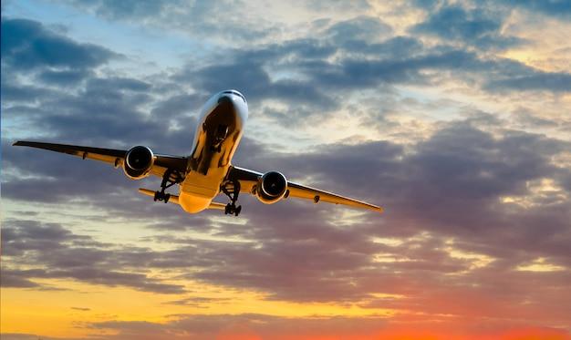 L'aereo va in decollo al tramonto sullo sfondo del cielo nuvoloso