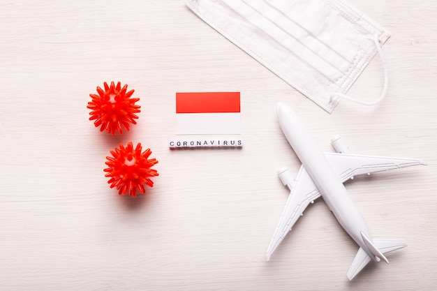 Modello di aereo e maschera e bandiera indonesia. pandemia di coronavirus. divieto di volo e frontiere chiuse per turisti e viaggiatori con coronavirus covid-19.