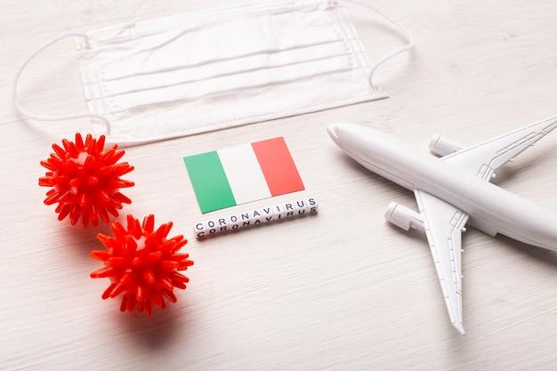 Modello di aereo e maschera e bandiera italia. pandemia di coronavirus. divieto di volo e frontiere chiuse per turisti e viaggiatori con coronavirus covid-19 provenienti da europa e asia.