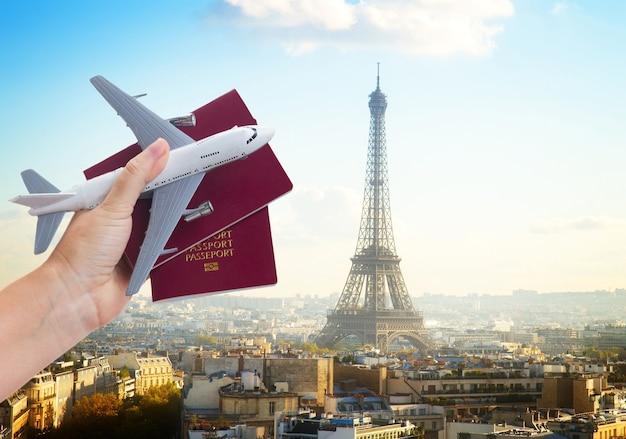 Concetto di viaggio aereo, mano che tiene i passaporti con l'aereo, paesaggio urbano di parigi francia in background