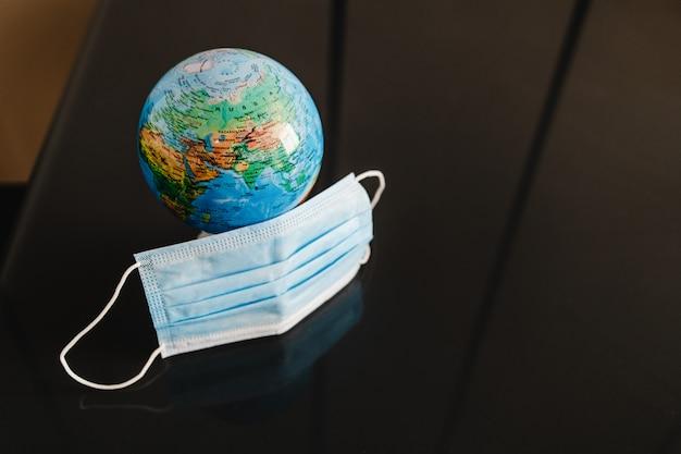 Globo del pianeta terra con maschera sulla scrivania