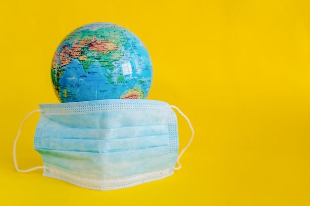 Globo del pianeta terra con maschera medica su sfondo giallo