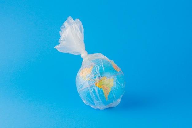 Pianeta terra dentro un sacchetto di plastica su sfondo blu.