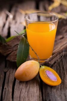 Frutta di plango o marian plum tropicale sud-est asiatico frutta e bicchiere di succo.
