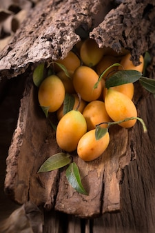 Frutta di plango o frutta tropicale dell'asia sud-orientale della prugna mariana su vecchio fondo di legno