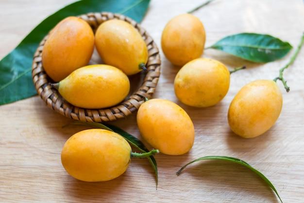 Plango, frutta tailandese della prugna mariana dolce su fondo di legno