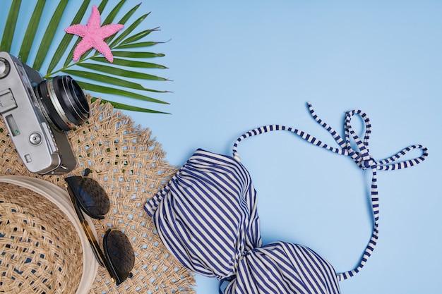 Pianificazione del viaggio e del viaggio. accessori da viaggio piatti laici su sfondo blu con bikini, fotocamera, cappello, occhiali da sole. vista dall'alto, viaggio o concetto di vacanza. sfondo estivo.