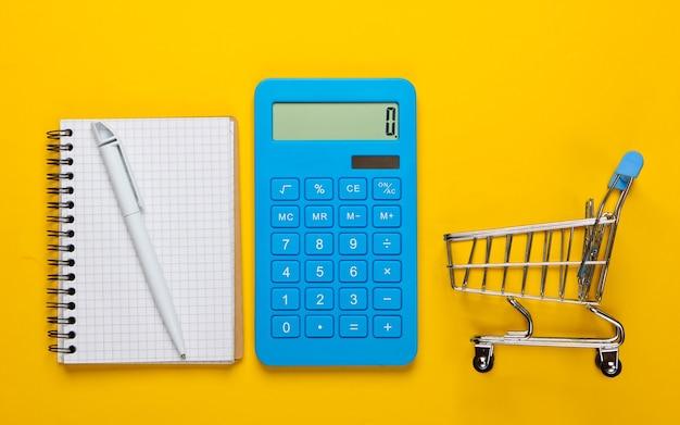 Pianificazione e calcolo dei costi di acquisto. calcolatrice con blocco note e carrello della spesa del supermercato su sfondo giallo. vista dall'alto