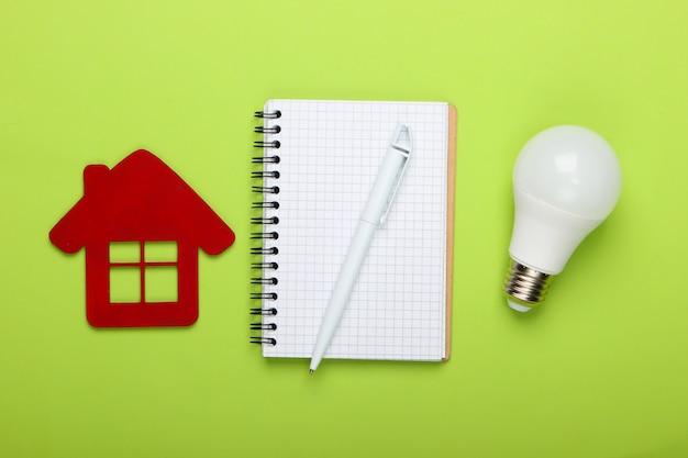 Pianificazione del risparmio energetico. statuetta di casa e lampadina a risparmio energetico, notebook su sfondo verde. vista dall'alto