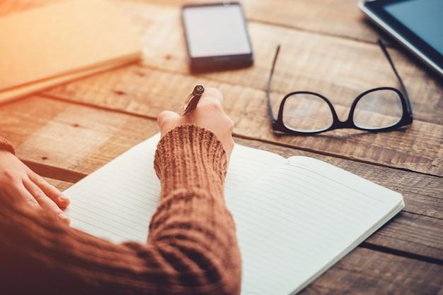 Pianificazione del nuovo giorno. immagine ravvicinata di una donna che scrive su un taccuino con spazio per le copie mentre è seduta al tavolo di legno grezzo