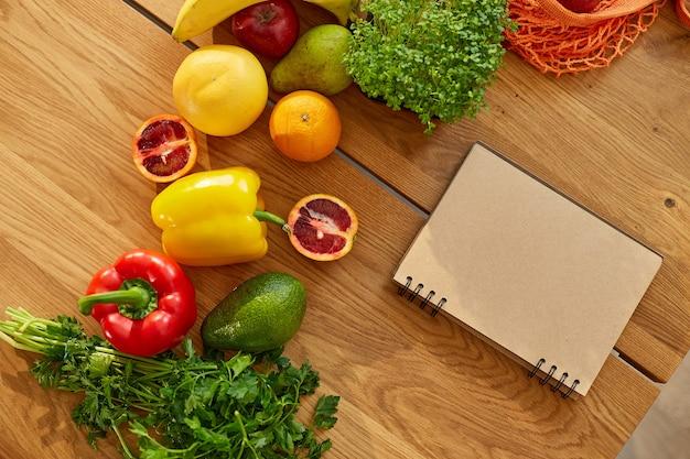 Taccuino di pianificazione, scrittura dei pasti settimanali su una nota del pianificatore dei pasti o un piano dietetico